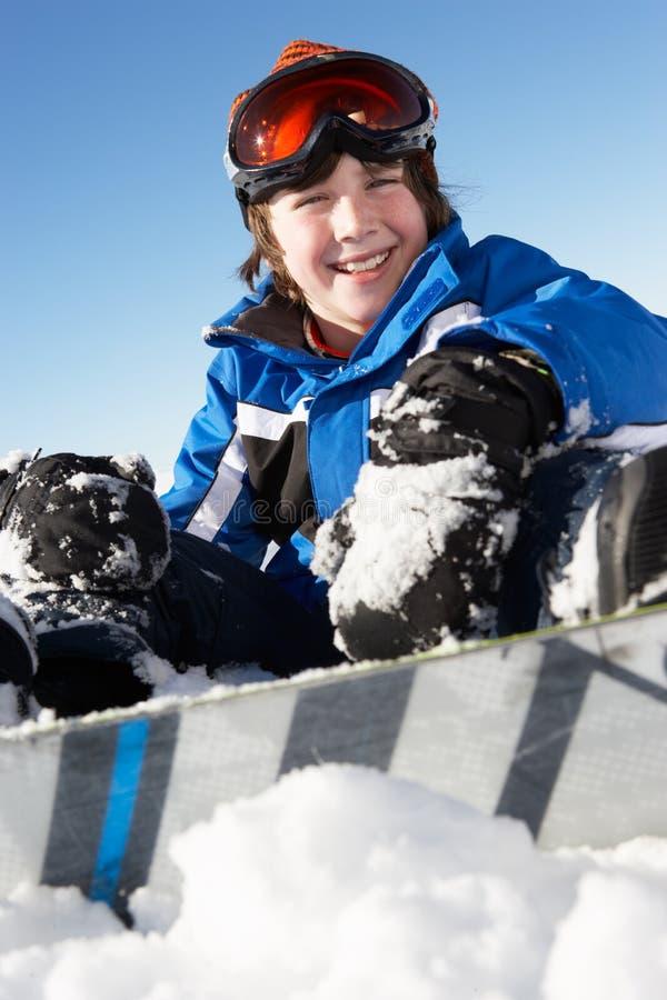 Ung pojke som sitter i Snow med snowboarden arkivfoton