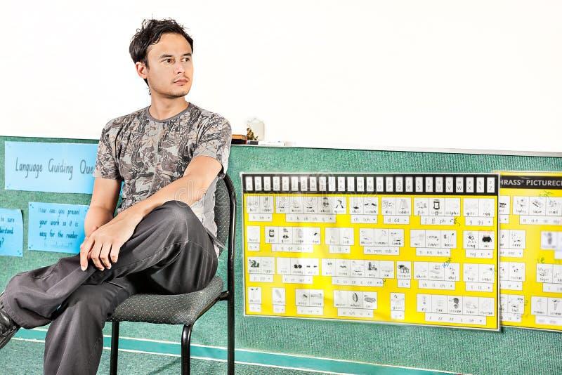 Ung pojke som sitter på en stol och att se bort arkivfoton