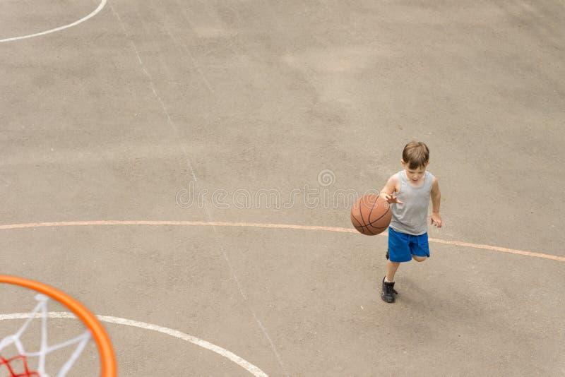 Ung pojke som spelar basketspring med bollen royaltyfri foto