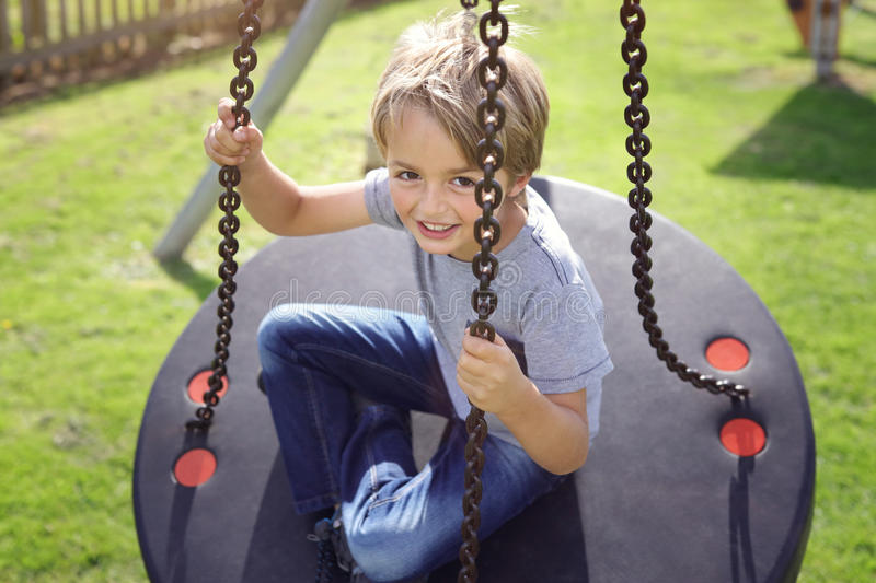 Ung pojke som spelar på en gunga royaltyfri bild