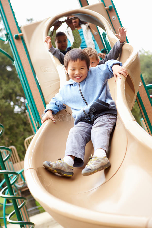 Ung pojke som spelar på glidbana i lekplats royaltyfri fotografi