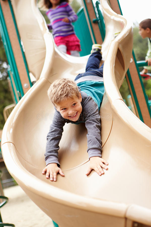 Ung pojke som spelar på glidbana i lekplats royaltyfri foto