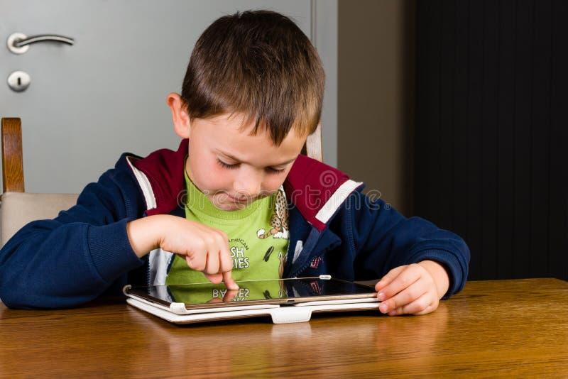 Ung pojke som spelar på minnestavladatoren royaltyfri fotografi