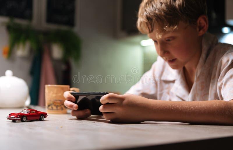 Ung pojke som spelar videospelet genom att använda smartphonen på köksbordet arkivbild
