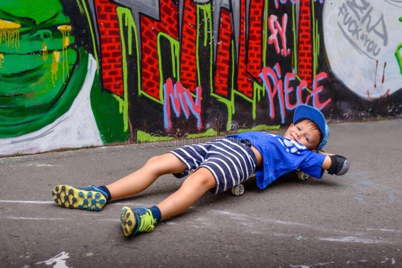 Ung pojke som tar en ta sig en tupplur på hans skateboard fotografering för bildbyråer