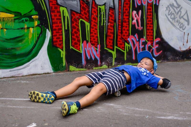 Ung pojke som tar en ta sig en tupplur på hans skateboard royaltyfri bild