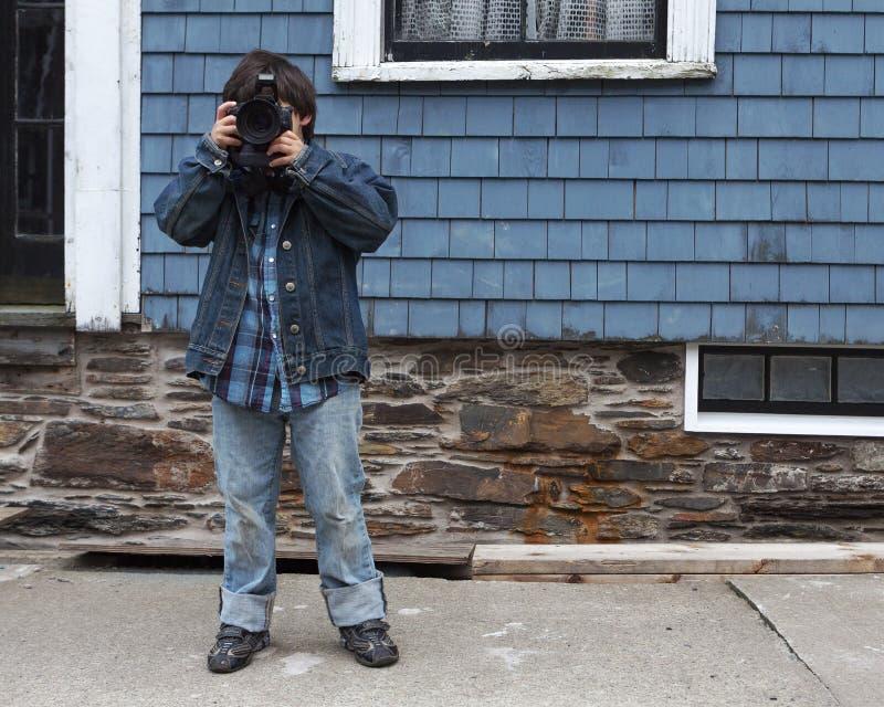 Ung pojke som tar ett foto med en Digital SLR kamera, bostads- stads- läge fotografering för bildbyråer