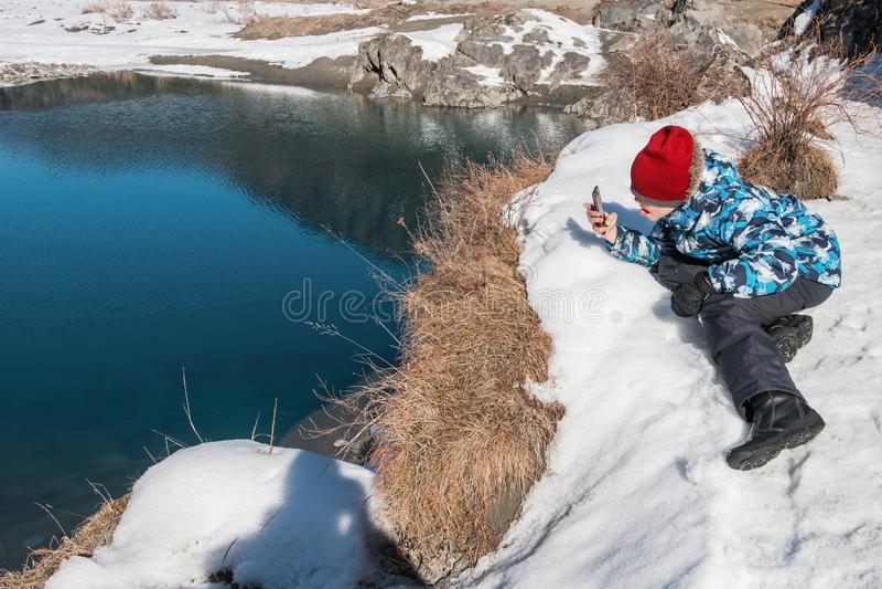 Ung pojke som tar foto på kustfloden arkivfoto