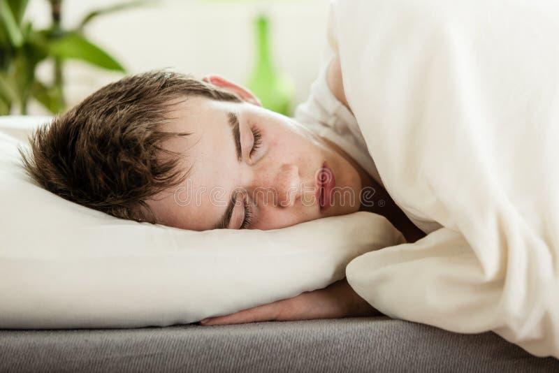 Ung pojke som tycker om en fridsam sömn arkivbild