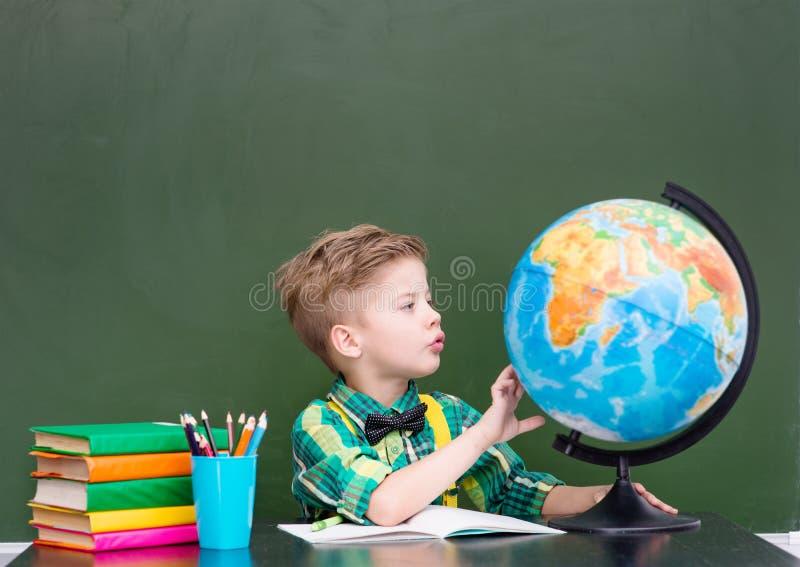 Ung pojke som undersöker jordklotet royaltyfria bilder