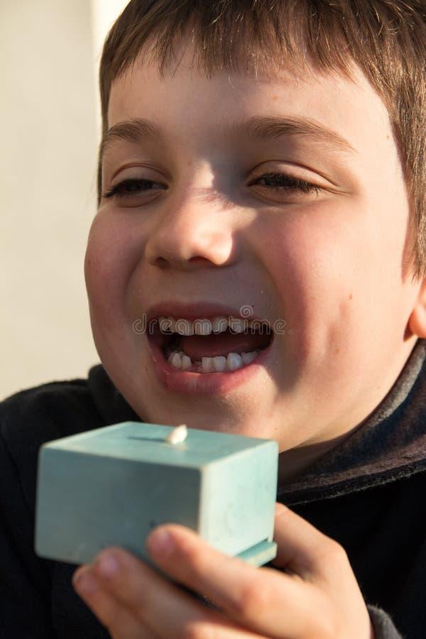 Ung pojke som visar hans första saknade tand arkivbilder