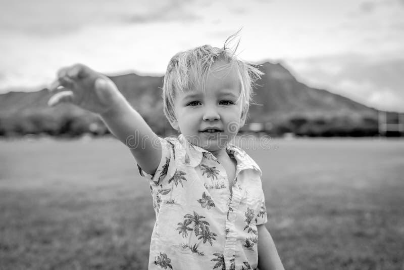 Ung pojke stående bärande Aloha Shirt i fält arkivbild