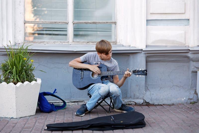 Ung pojkegatamusiker som spelar den akustiska gitarren på gatan arkivbild