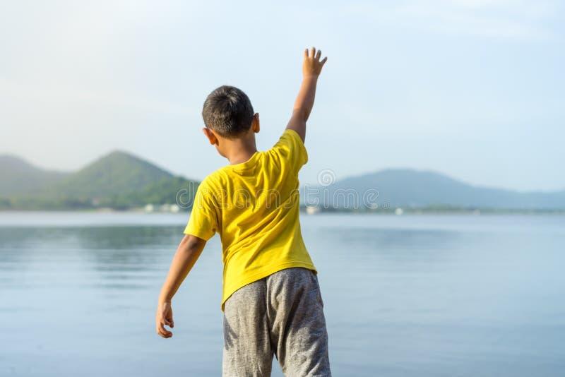 Ung pojkekaststen in i vattnet på pang den Pra behållaren i su royaltyfria foton