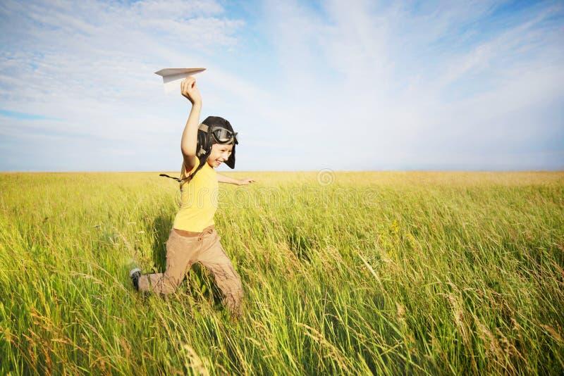 Ung pojkespring med det pappers- flygplanet royaltyfria bilder