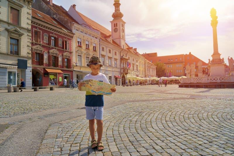 Ung pojketurist med stadsöversiktsstaget på den gamla europeiska gatan royaltyfria bilder