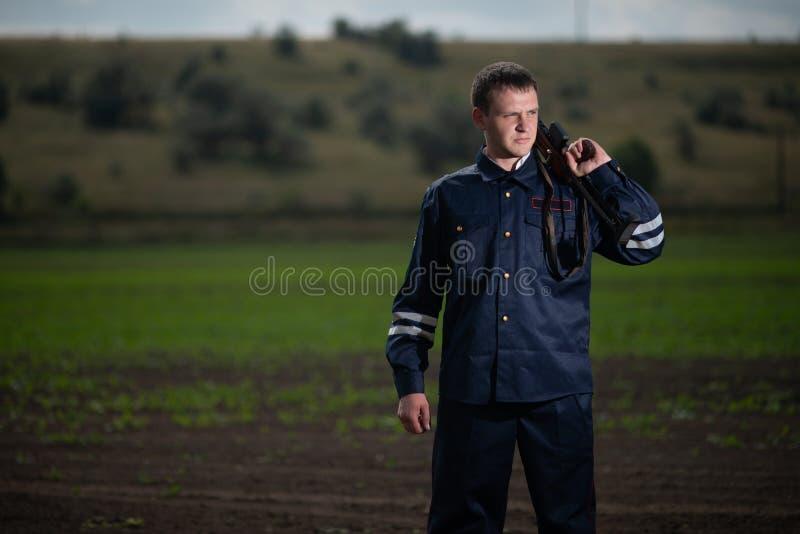 Ung polis i likformig, med vapnet i hand på lantlig landskapbakgrund royaltyfria bilder