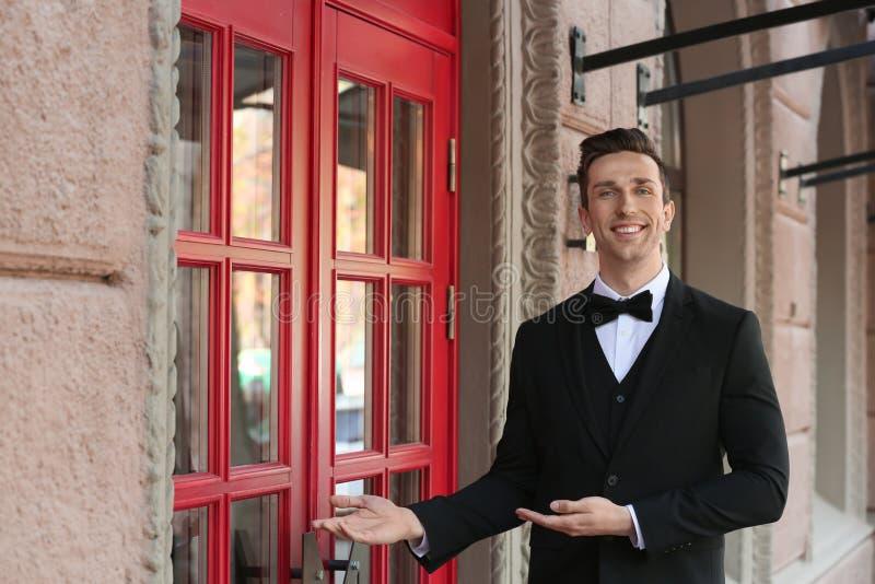 Ung portvakt i den eleganta dräkten som står den near restaurangen royaltyfria bilder