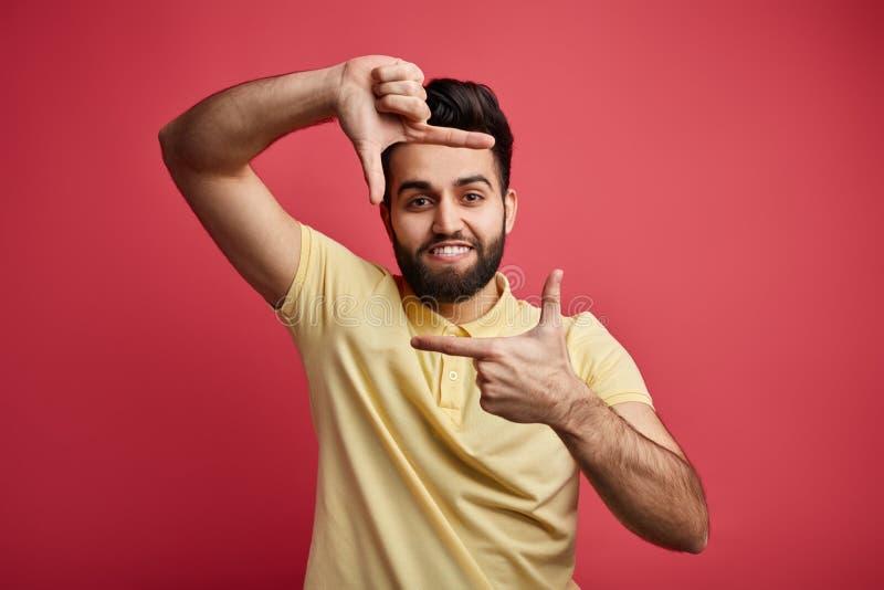 Ung positiv man i den gula T-tröja som gör ramen med hans händer royaltyfri bild