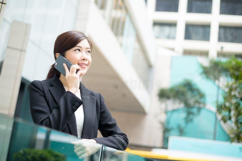Ung pratstund för affärskvinna på mobiltelefonen royaltyfri bild