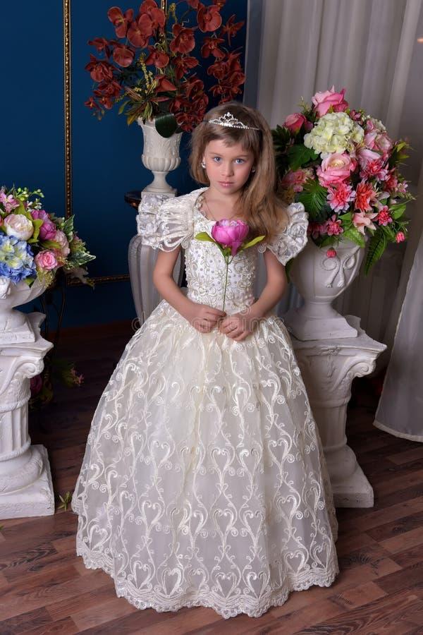 Ung prinsessa i en vit klänning med en tiara på hennes huvud arkivbilder