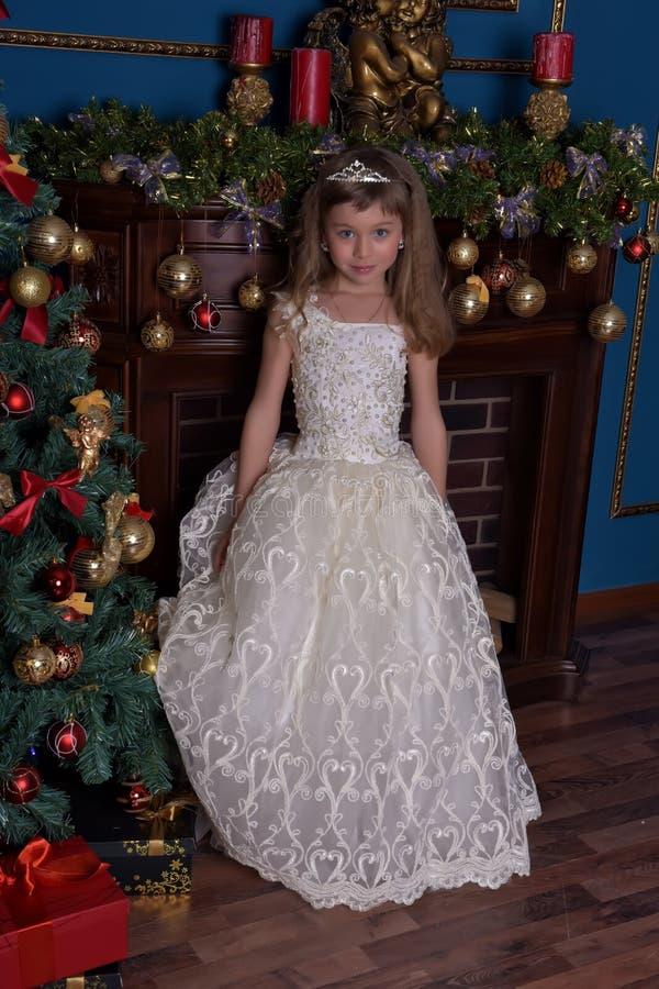 Ung prinsessa i en vit klänning med en tiara på hennes huvud på julgranen royaltyfri bild