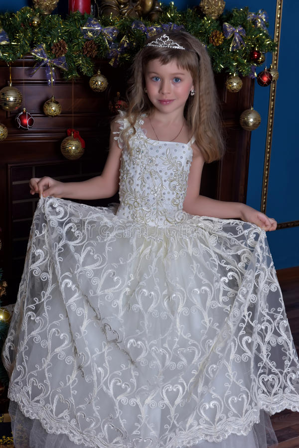 Ung prinsessa i en vit klänning med en tiara på hennes huvud på julgranen royaltyfri fotografi