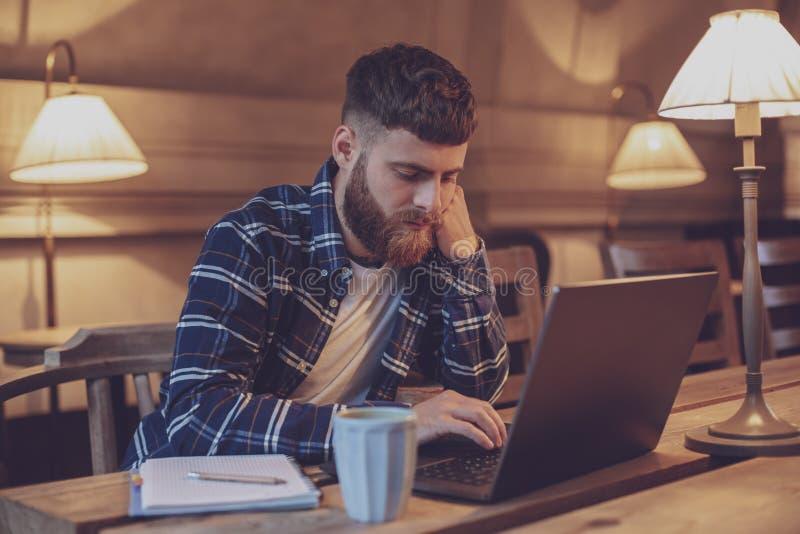 Ung professionell som surfar internet på hans bärbar dator i ett kafé arkivbilder