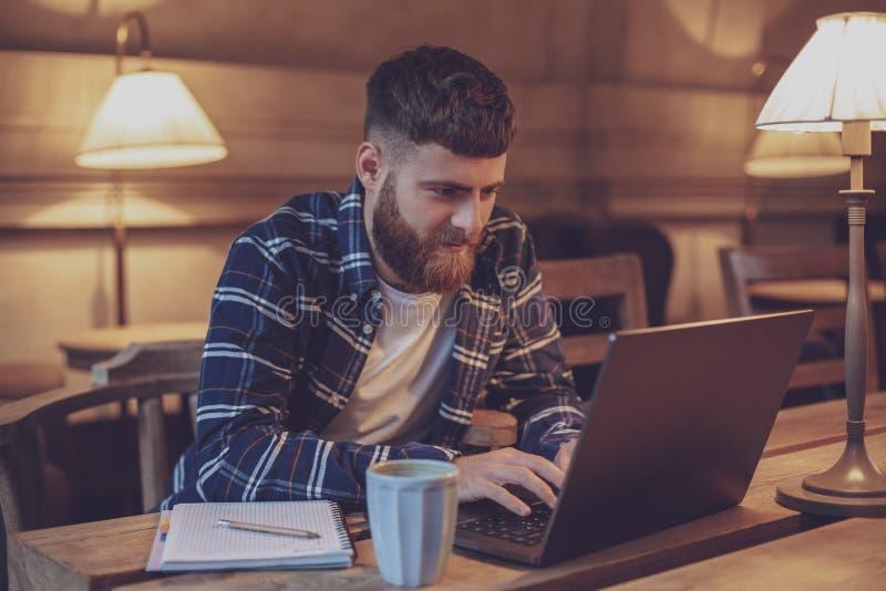 Ung professionell som surfar internet på hans bärbar dator i ett kafé royaltyfria foton