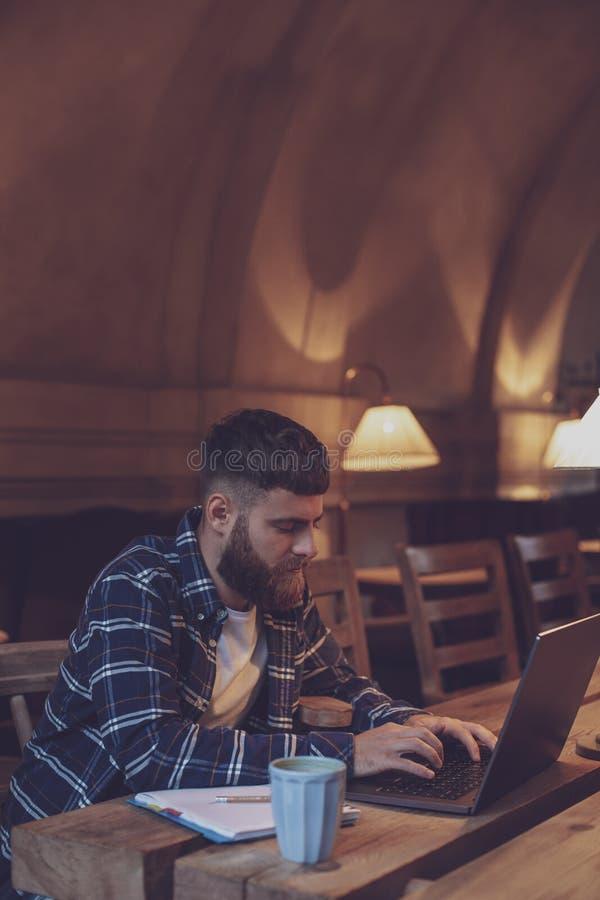 Ung professionell som surfar internet på hans bärbar dator i ett kafé royaltyfri foto