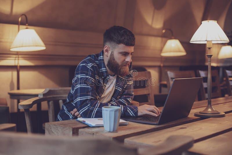 Ung professionell som surfar internet på hans bärbar dator i ett kafé arkivfoton