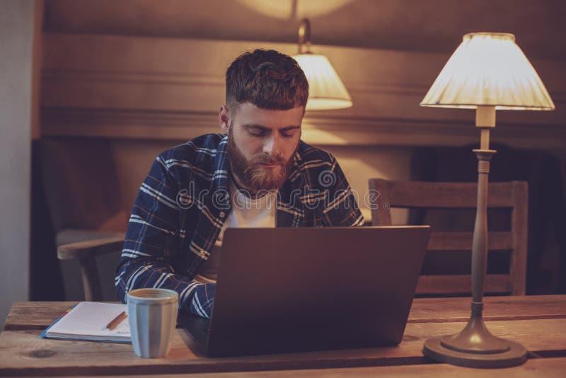 Ung professionell som surfar internet på hans bärbar dator i ett kafé arkivbild