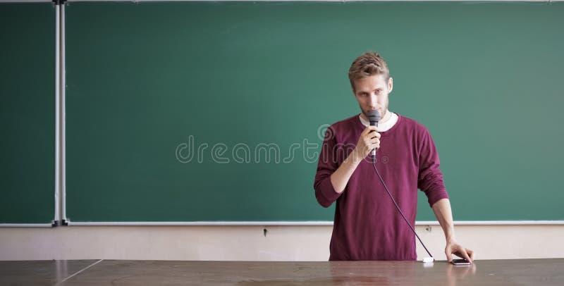 Ung professorlärare som talar med mikrofonen i hörsalen som står den near svart tavla royaltyfri fotografi
