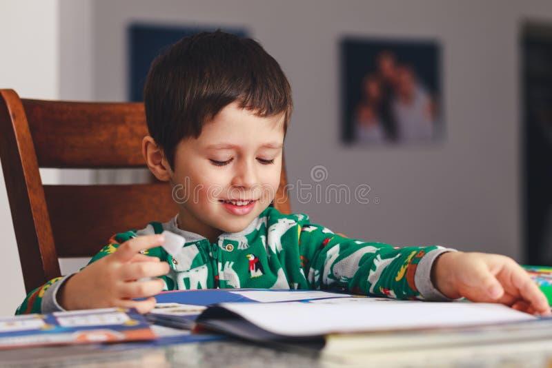 Ung pys som läser en bok, medan sitta på tabell, inomhus s arkivfoton