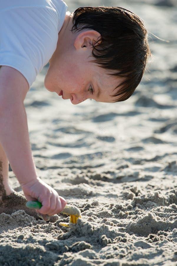 Ung pys som spelar med sanden och den byggande sandslotten på stranden nära havet arkivfoto