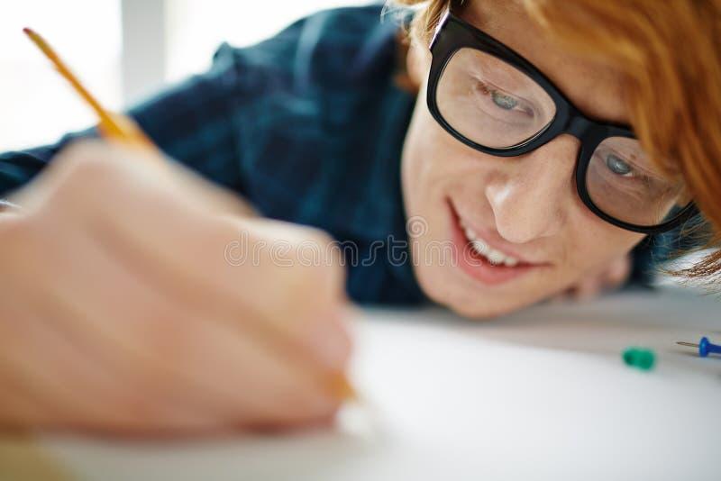 Ung röd haired manteckning med inspiration royaltyfri bild