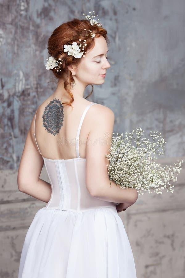 Ung rödhårig brud i elegant bröllopsklänning Hon står med henne tillbaka till tittaren Hon ögon är drömlikt stängt royaltyfria foton