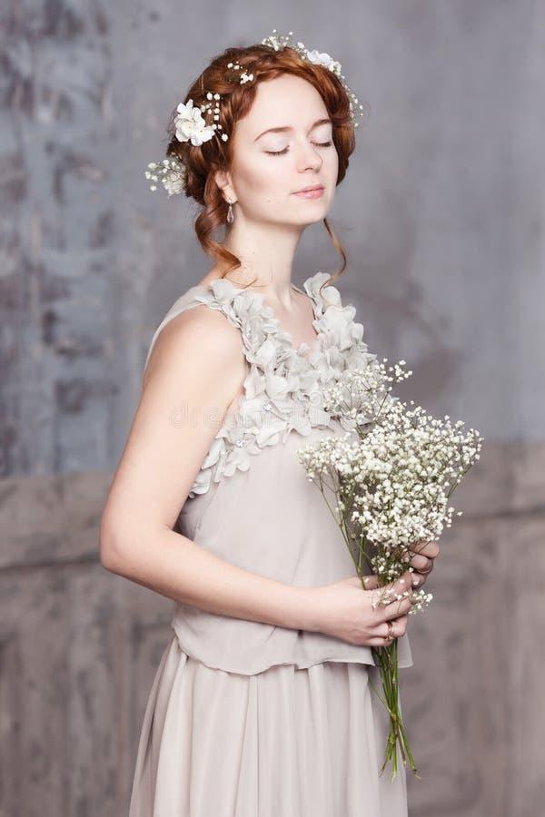 Ung rödhårig brud i pärla-grå färger klänning Hon står, som henne, är ögon drömlikt stängt, henne rymmer en bukett av vita vildbl arkivfoto