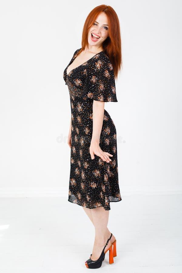 Ung rödhårig flicka i en svart klänningdans royaltyfria bilder