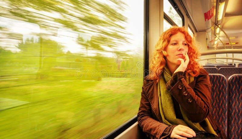 Ung rödhårig härlig sexig kvinna som sitter dagdrömma att dagdrömma i en rörande pendeltåg med kopieringsutrymme royaltyfri foto