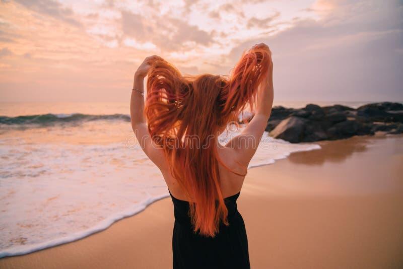 Ung rödhårig kvinna med flyghår på havet, bakre sikt royaltyfri fotografi