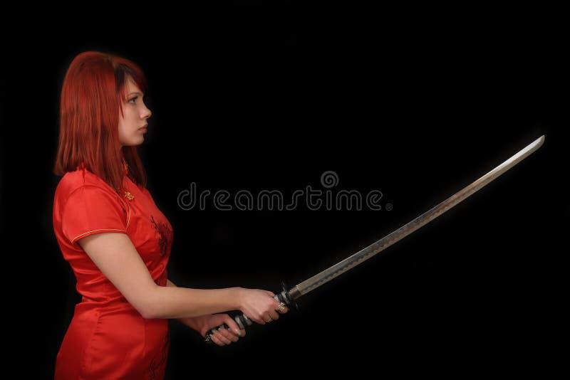 Ung rödhårig manflicka med katana fotografering för bildbyråer