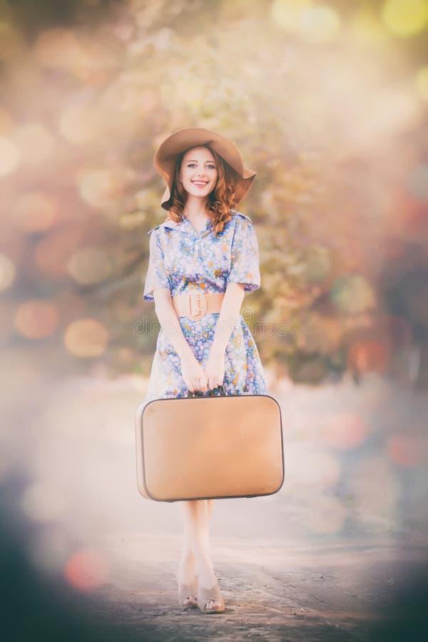 Ung rödhårig mankvinna i klänning med resväskan royaltyfria foton
