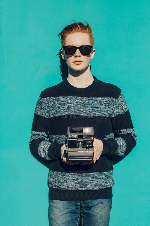 Ung rödhårig manman i en tröja och jeans och solglasögon som står bredvid turkosväggen och tar fototappningkamera varm summ royaltyfri fotografi