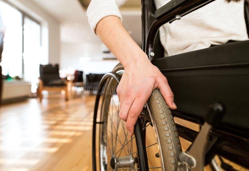 Ung rörelsehindrad kvinna i rullstol hemma i vardagsrum fotografering för bildbyråer