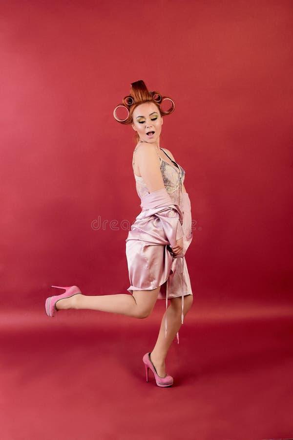 Ung r?dh?rig mankvinna med den ikl?dda negligen f?r papiljotter, peignoir, kl? kappa som poserar p? en burgundy bakgrund arkivbilder