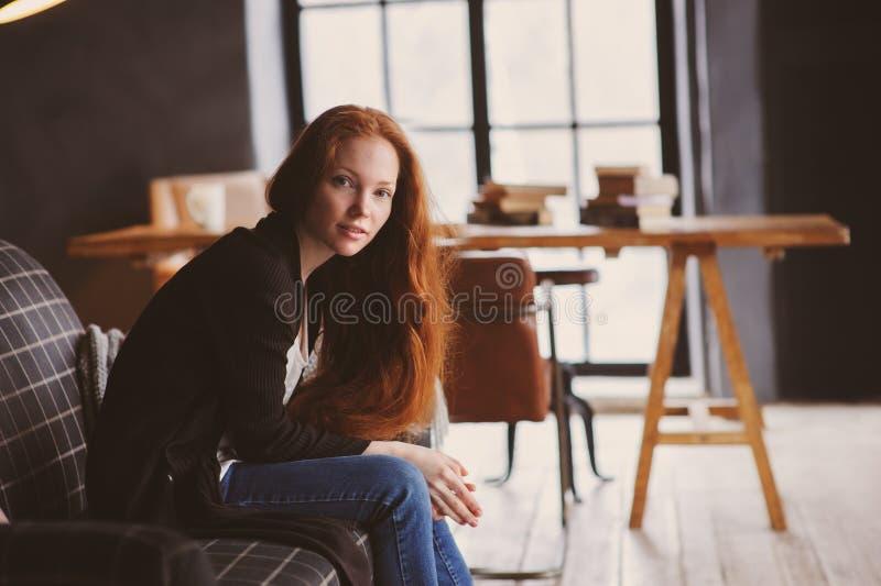 ung readheadkvinna som hemma kopplar av på den hemtrevliga soffan, den iklädda tillfälliga tröjan och jeans arkivbild