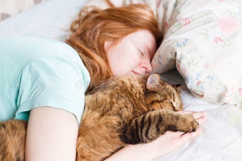 Ung redhairkvinna som sover med katten arkivbild