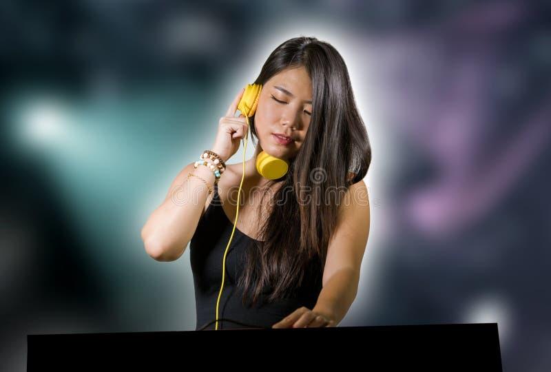Ung remixing musik för härlig och attraktiv asiatisk japansk discjockeykvinna på bärande hörlurar för nattklubb, i att klub royaltyfri bild