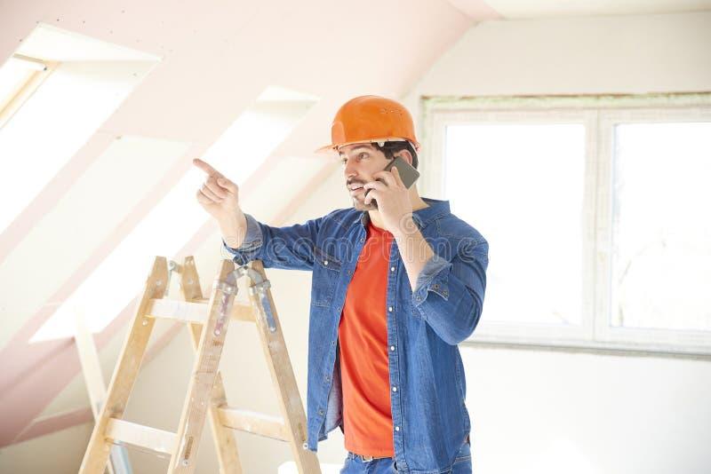 Ung repairman som använder hans mobiltelefon på konstruktionsplatsen royaltyfria bilder